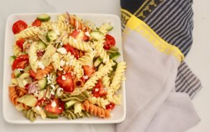 Greek Pasta salad loaded with vegetables and tons of layers of flavor. The perfect salad for your Summer get together.